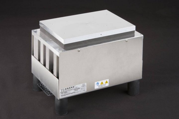 Three-quarter view of large thermoelectric cold plate cooler/heater incorporating six thermoelectric modules. The cooled aluminum plate on the front and waste heat is exhausted to high-density fins on the back. Fins are fan cooled. The fan air enters on the middle back and exhausts on sides. The cooler incorporates legs which lift the fan's air inlet off of a table top, so the cooler can be operated directly on a table. It operates on 24 volts DC and removes 204 watts of heat at a 0°C temperature difference relative to ambient. Internal extender blocks improve the heat pumping capacity at larger temperature differences. Can heat to 100°C without damaging the cooler.
