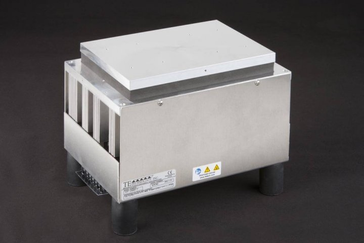 Three-quarter view of large thermoelectric cold plate cooler/heater incorporating six thermoelectric modules. The cooled aluminum plate on the front and waste heat is exhausted to high-density fins on the back. Fins are fan cooled. The fan air enters on the middle back and exhausts on sides. The cooler incorporates legs which lift the fan's air inlet off of a table top, so the cooler can be operated directly on a table. It operates on 24 volts DC and removes 204 watts of heat at a 0°C temperature difference relative to ambient. Internal extender blocks improve the heat pumping capacity at larger temperature differences.